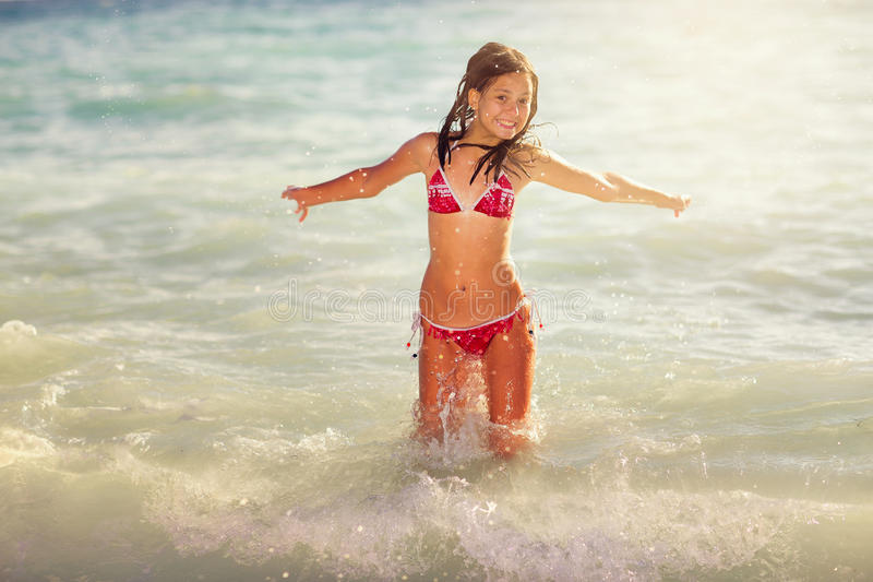 A menina feliz salta nas ondas do mar imagem de stock