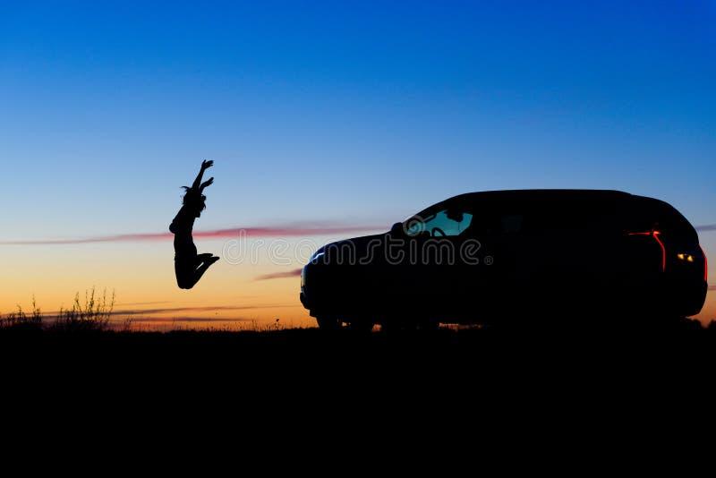 A menina feliz salta perto de SUV fotos de stock