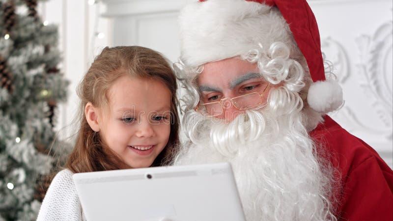 A menina feliz Santa surpreendida exibição apresenta na tabuleta imagens de stock royalty free