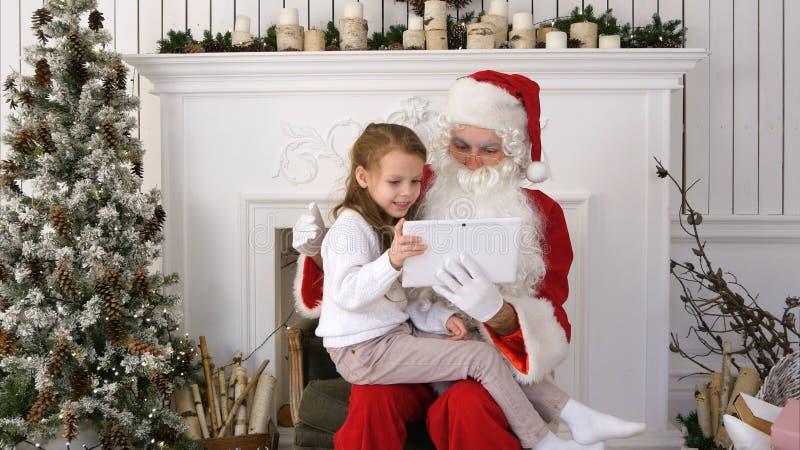 A menina feliz Santa surpreendida exibição apresenta na tabuleta foto de stock