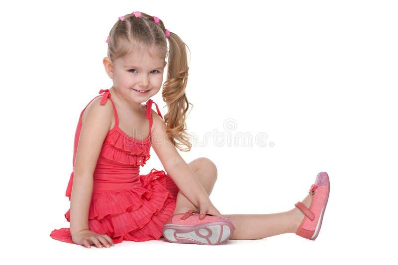 A menina feliz senta-se no assoalho imagens de stock royalty free