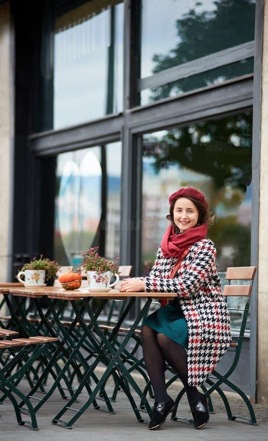 A menina feliz senta-se no café na rua de Budapest imagens de stock royalty free