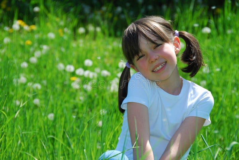 Menina feliz sentada no campo fotografia de stock royalty free