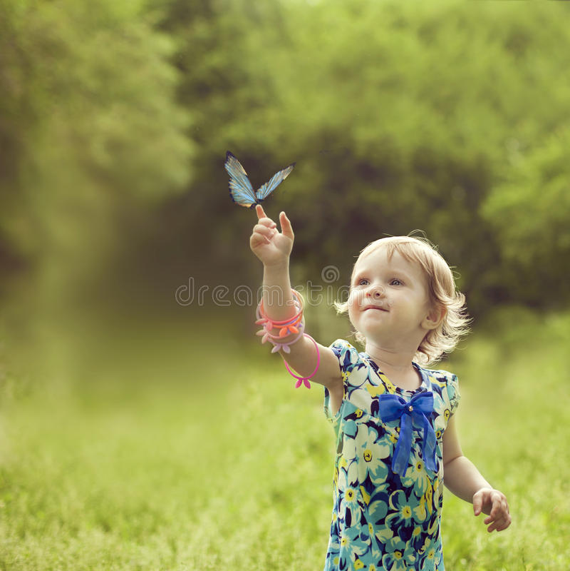 A menina feliz sentou-se no braço de uma borboleta bonita fotos de stock