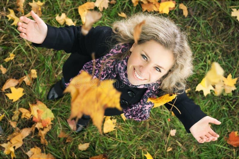 A menina feliz sob a árvore com queda folheia foto de stock