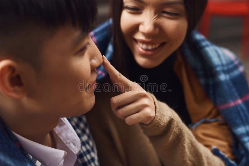 A menina feliz toca em um nariz do indivíduo fotografia de stock
