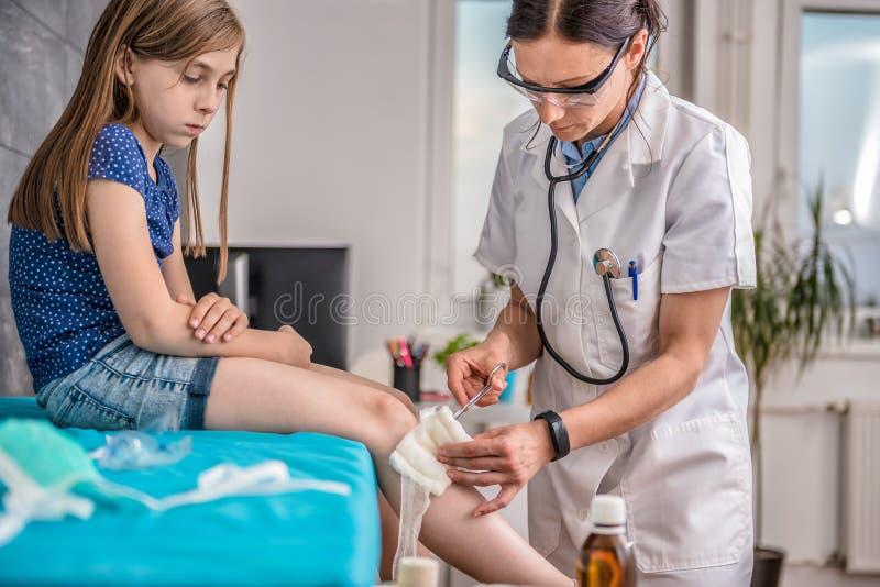 Menina ferida que recebe primeiros socorros fotos de stock
