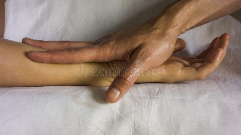 A menina fez massagens sua mão fotos de stock