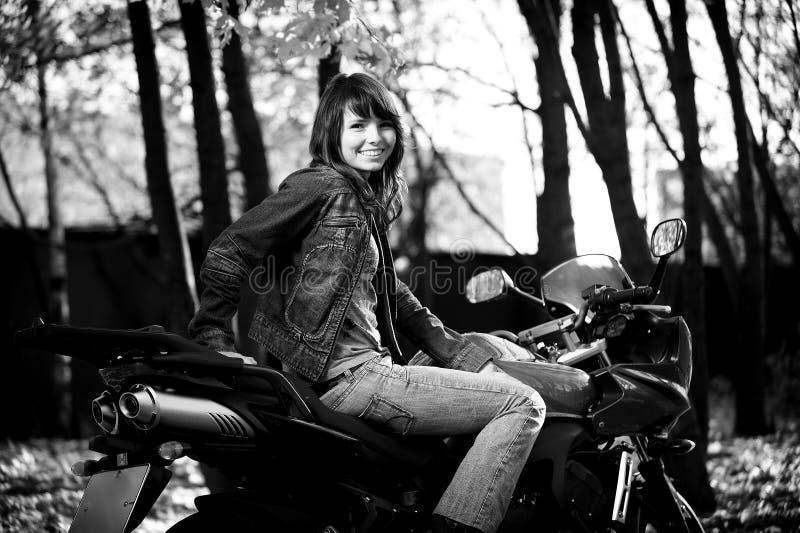 A menina fina em uma motocicleta imagem de stock royalty free