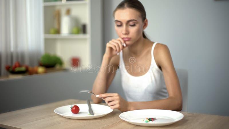 Menina fina que olha os comprimidos da anti-obesidade, obsessão com perda de peso, apego imagens de stock
