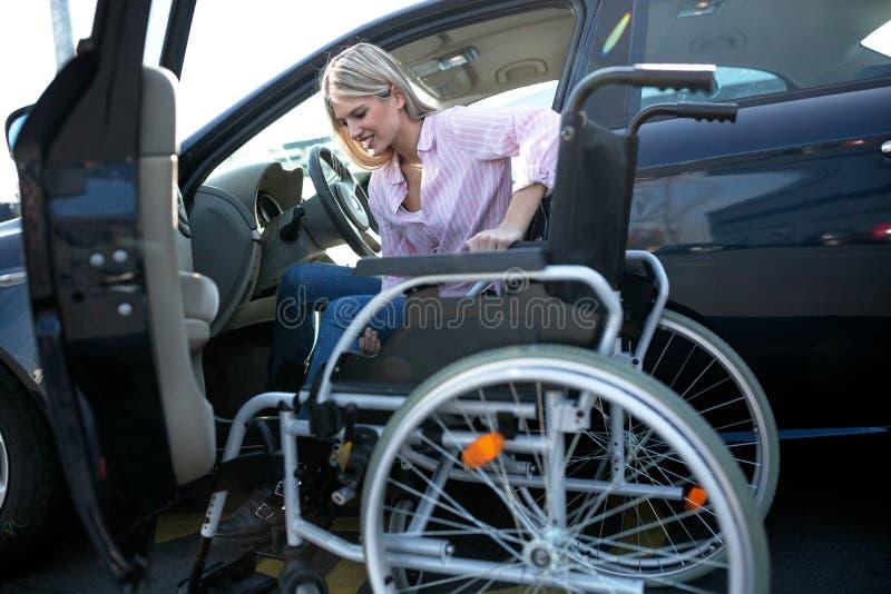 Menina fisicamente desafiada na camisa cor-de-rosa que move-se do veículo para a cadeira de rodas foto de stock