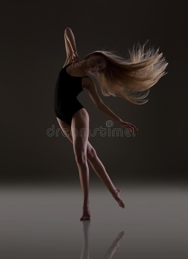 Menina flexível com dança longa do cabelo louro Cabelo do v?o fotografia de stock royalty free