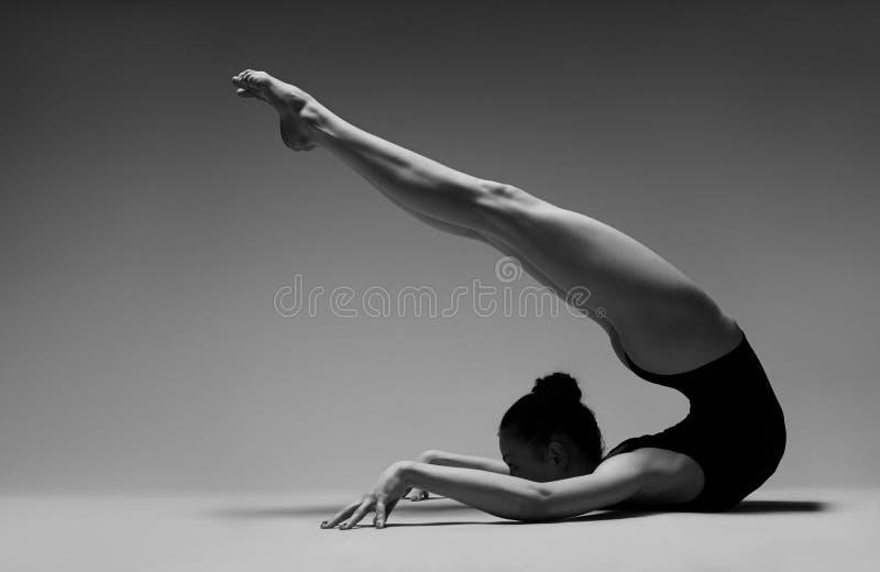 Menina flexível em um roupa de banho preto imagem de stock