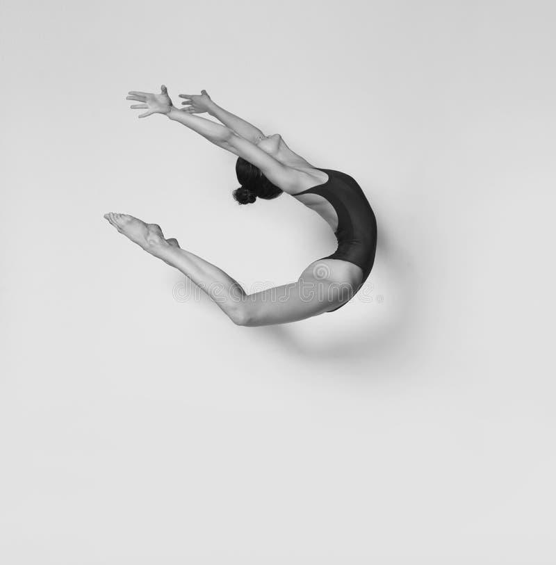 A menina flexível em um roupa de banho preto faz um salto bonito fotos de stock royalty free