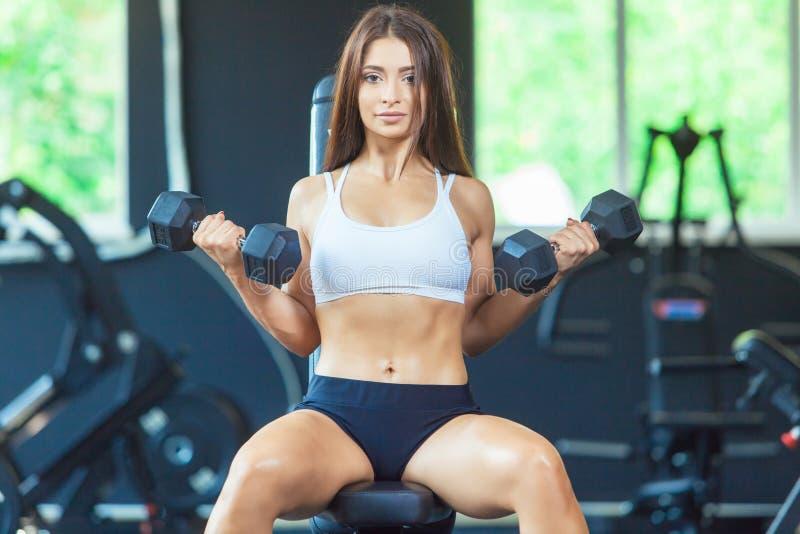 Menina focalizada desportiva nova da aptidão da forma atrativa que faz exercícios do bíceps ao sentar-se no instrumento de formaç fotografia de stock