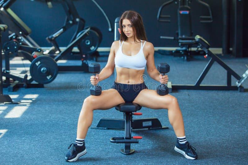 Menina focalizada desportiva nova da aptidão da forma atrativa que faz exercícios do bíceps ao sentar-se no instrumento de formaç foto de stock