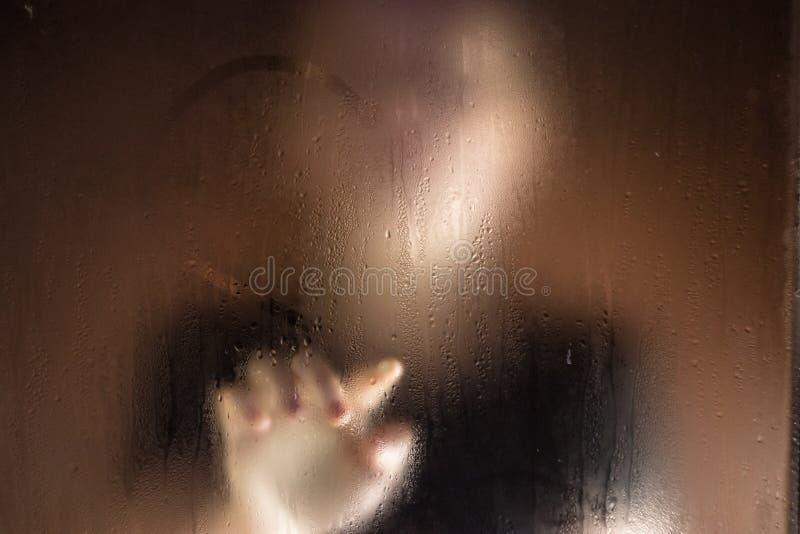 A menina fora da janela tira o coração do dedo no vidro molhado As meninas para fora focalizam foto de stock