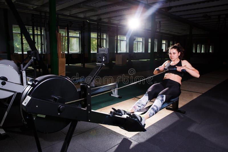 Menina forte nova que faz um exercício em uma máquina de enfileiramento Para treinar os cardio- braços, traseiro Conceitos ostent foto de stock
