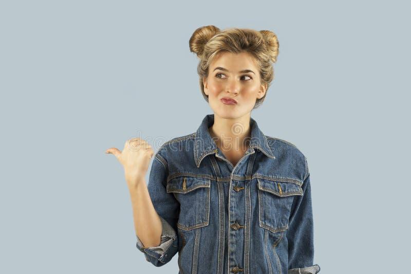 A menina fortemente emocional bonita nova mostra gestos diferentes em um fundo azul isolado Conceito de emoções humanas fotografia de stock