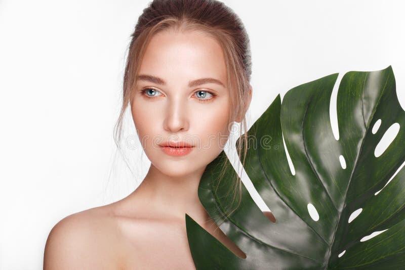 A menina fresca bonita com a pele perfeita, natural comp?e e as folhas verdes Face da beleza imagens de stock royalty free