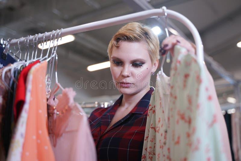 A menina fresca bonita em um vestido elegante que anda na loja e escolhe a roupa nova, olhando trajes na moda em ganchos dentro fotografia de stock
