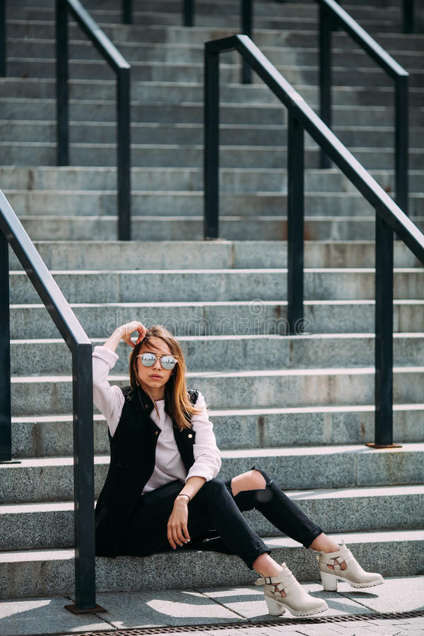 Menina fresca do moderno da forma nos óculos de sol fundo urbano, olhar da forma Assento modelo nas escadas foto de stock