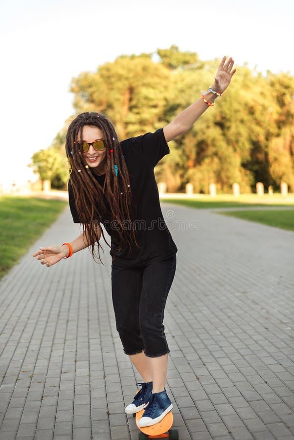 A menina fresca mantém seu equilíbrio no skate no parque foto de stock