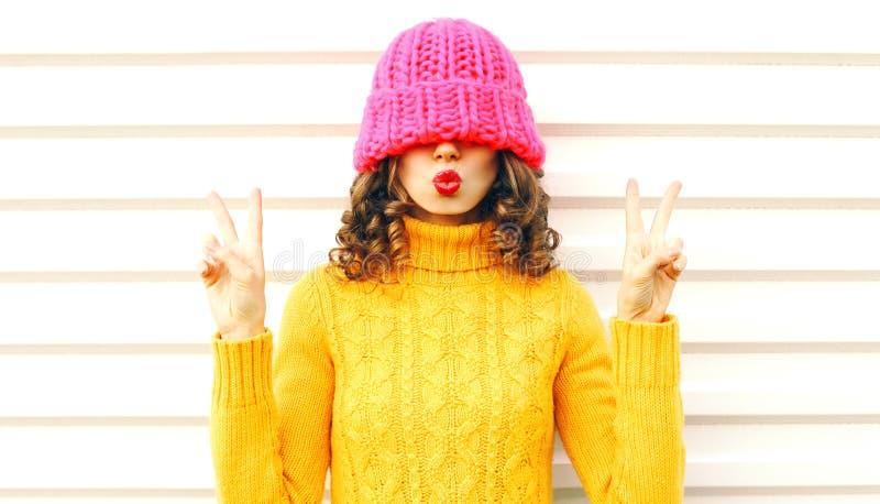 A menina fresca que funde os bordos vermelhos faz o beijo do ar que veste o chapéu cor-de-rosa feito malha colorido, camiseta ama fotografia de stock royalty free