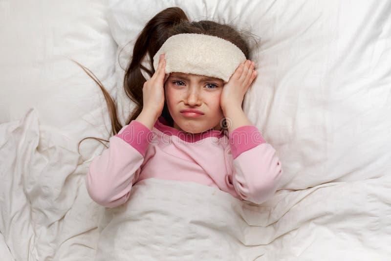 A menina fria doente da criança pequena encontra-se na cama imagem de stock royalty free