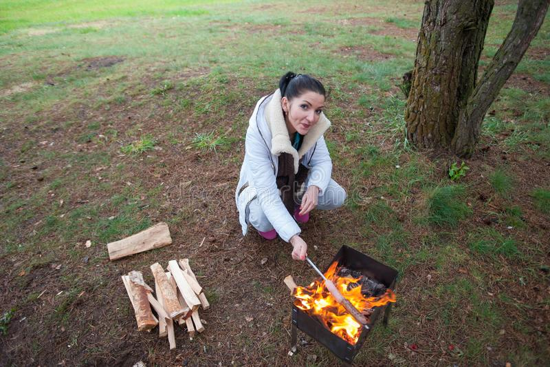 A menina frita salsichas na natureza Uma mulher perto das salsichas das fritadas do fogo no alimento delicioso da fogueira da flo fotos de stock
