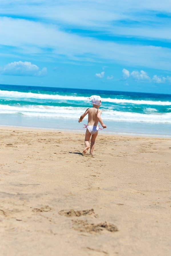 A menina funciona para fora ao mar na areia fotografia de stock royalty free