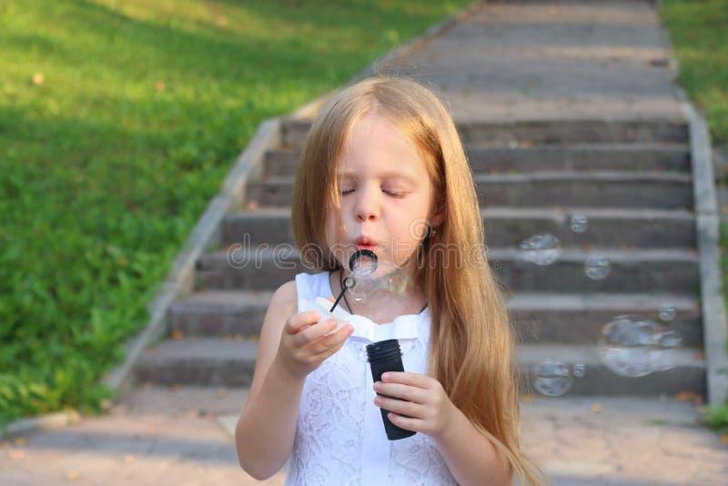 A menina funde bolhas perto das escadas no parque ensolarado verde imagens de stock royalty free
