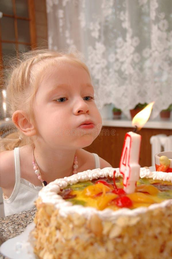 A menina funde em uma vela em um bolo foto de stock royalty free
