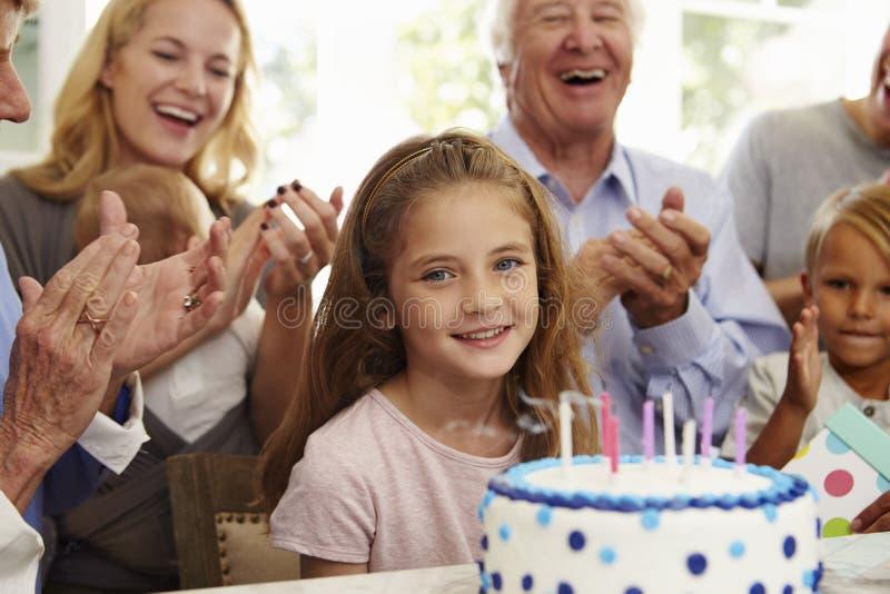 A menina funde para fora velas do bolo de aniversário no partido da família fotos de stock