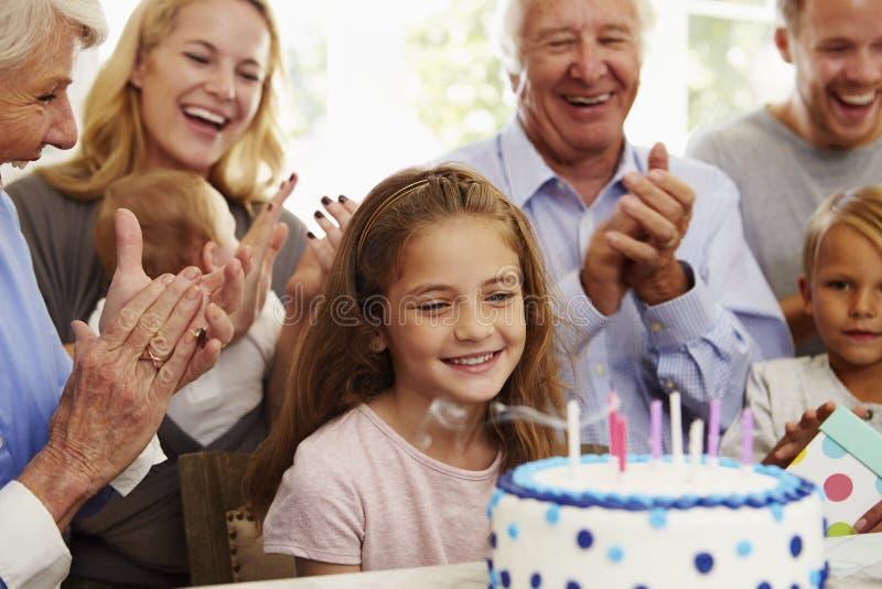 A menina funde para fora velas do bolo de aniversário no partido da família foto de stock