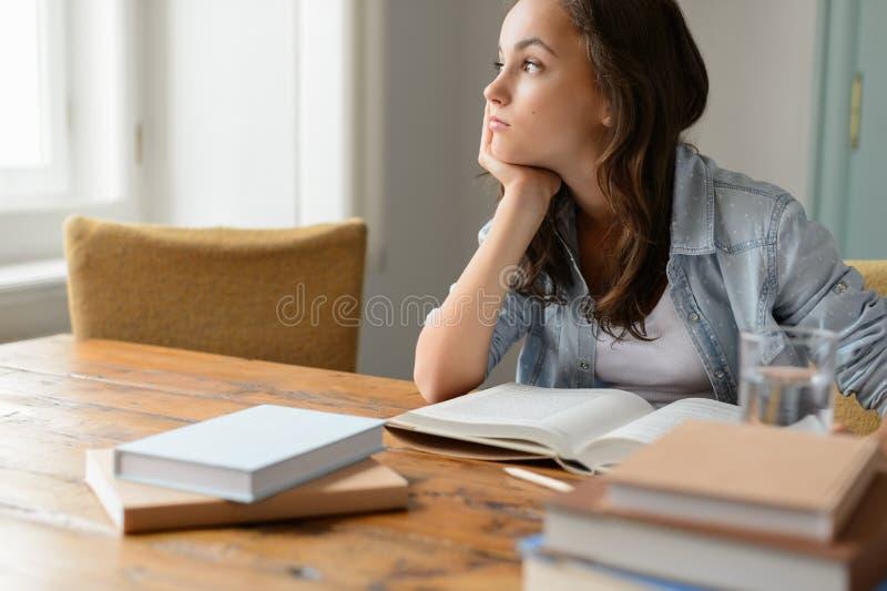 Menina furada do estudante que senta em casa a vista afastado foto de stock