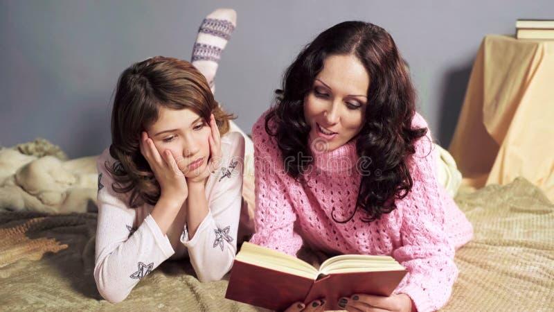 A menina furou com livro de histórias sua leitura da mãe antes das horas de dormir, unidade fotografia de stock royalty free