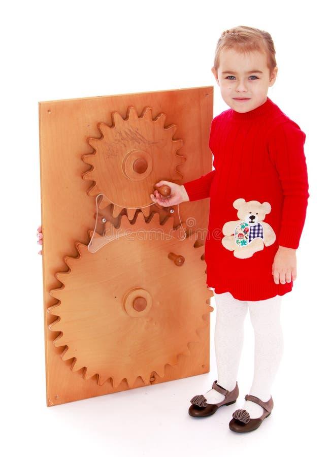 A menina gerencie à mão a engrenagem roda dentro Montessori fotografia de stock