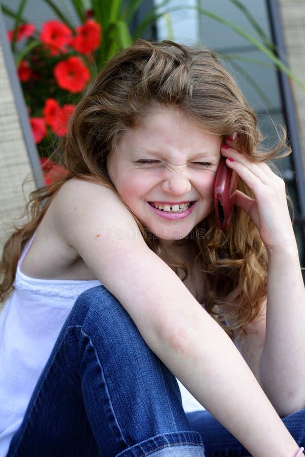 Menina Giggling no telefone imagens de stock