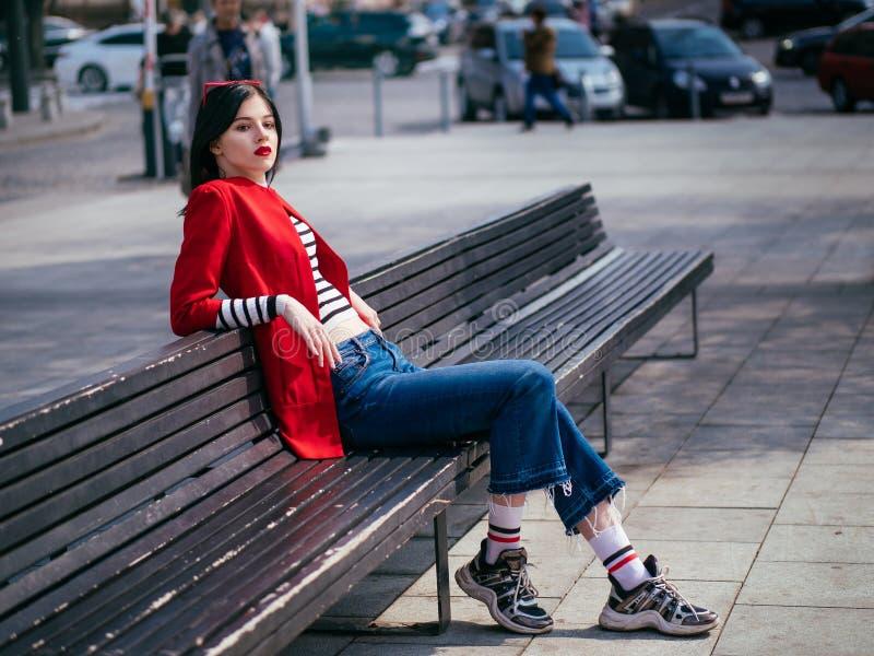 Menina glamoroso bonita de brunete em um levantamento vermelho do revestimento imagens de stock
