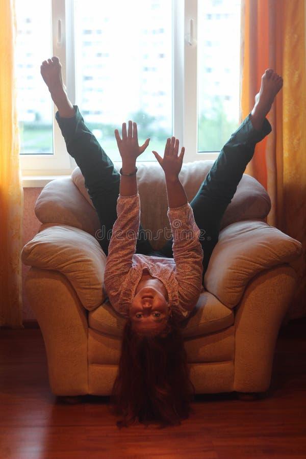 Menina gorda alegre que engana ao redor no sofá imagem de stock royalty free