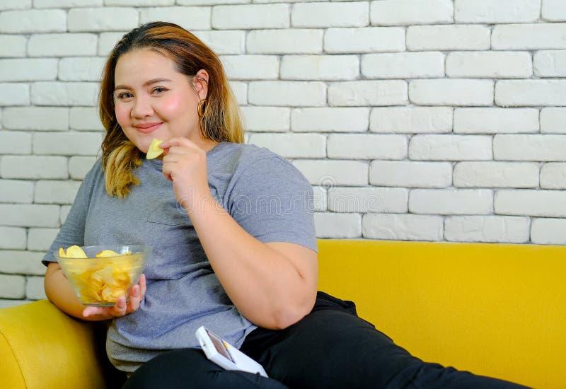 A menina gorda com t-shirt cinzento está comendo microplaquetas de batatas e está sentando-se no sofá amarelo durante o programa  fotos de stock
