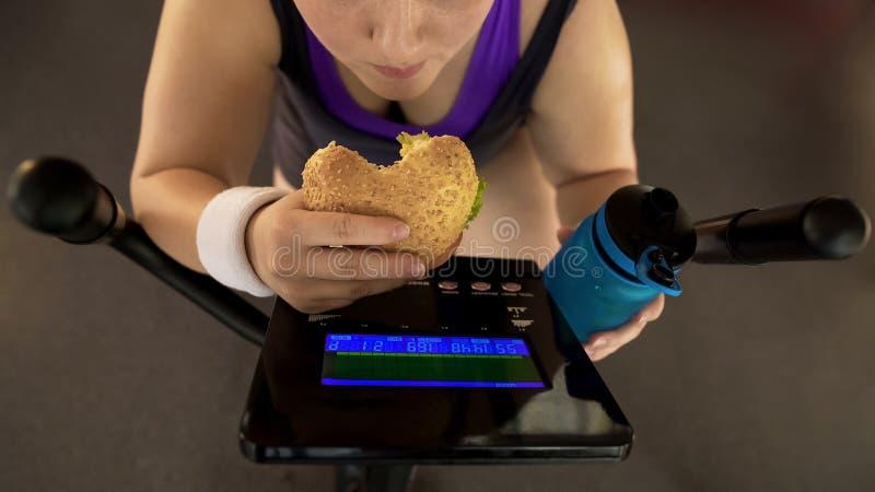 Menina gorda que come demais o hamburguer e a água potável ao montar a bicicleta de exercício imagens de stock