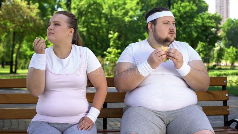 Menina gorda que come a maçã, homem obeso que come o hamburguer, escolha individual do alimento apropriado imagens de stock