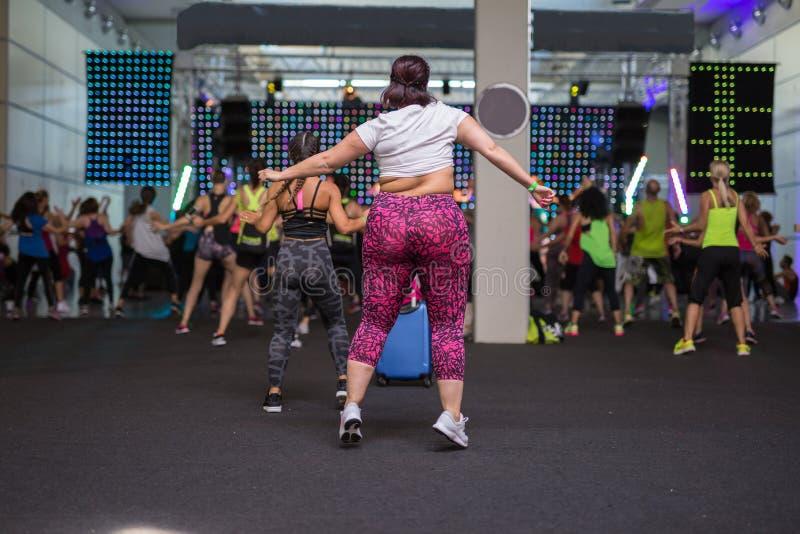 Menina gorda que faz a aptidão na classe no Gym: Exercício com música imagens de stock royalty free