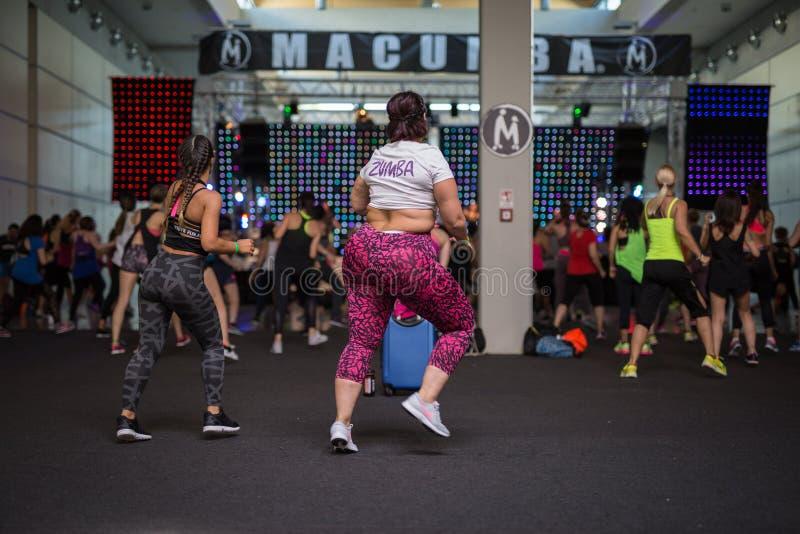 Menina gorda que faz a aptidão na classe no Gym: Exercício com música fotos de stock