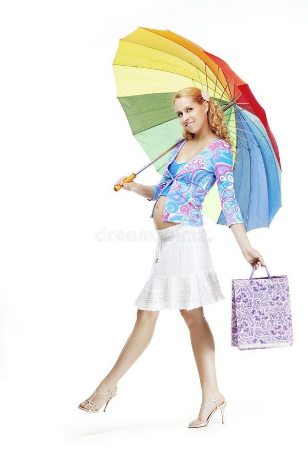 Menina grávida bonita com um guarda-chuva do arco-íris foto de stock