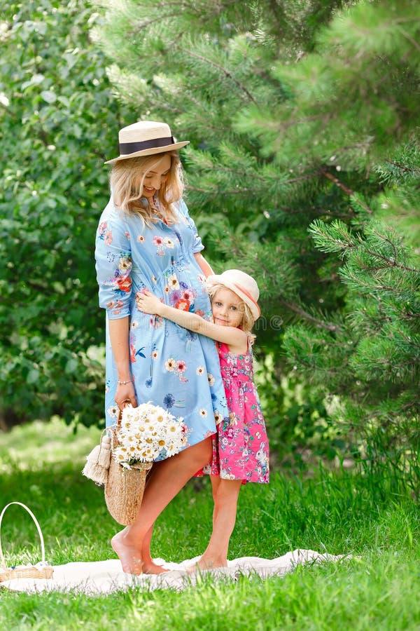 A menina grávida bonita em um chapéu de palha está estando com um ramalhete de flores do verão ao lado de sua filha pequena e est fotografia de stock
