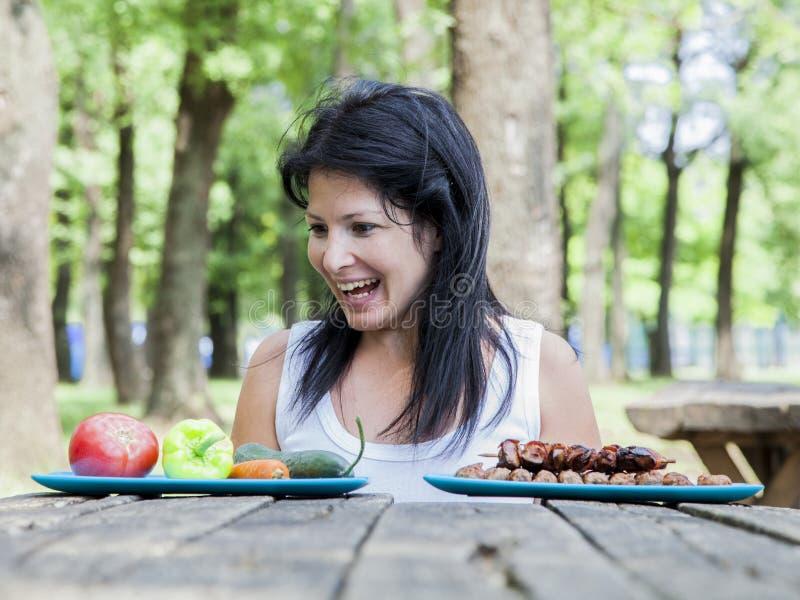 Menina grávida dos jovens que escolhe o alimento para sua refeição fotografia de stock royalty free