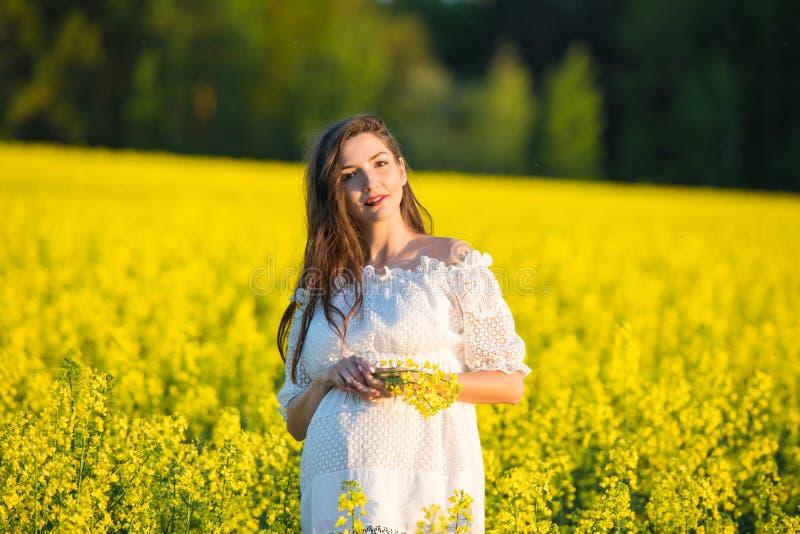 Menina grávida em um fundo amarelo os olhares em seu estômago, imaginam seu nascituro Conceito de maternidade fotos de stock royalty free